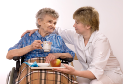 a nurse assisting an old woman to her meal